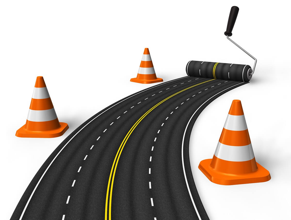 cartoon image of three traffic cones and a four-lane road being rolled out by a paint roller