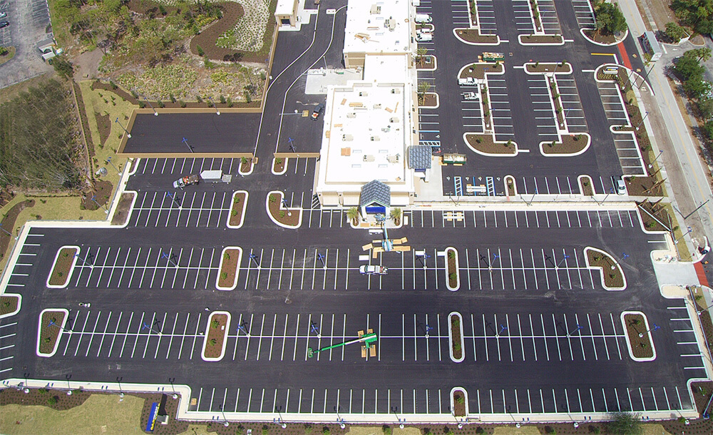 aerial image of parking lot with white building in center